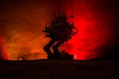 Silhouet van reuzerobot Futuristische tank in actie met de mistige achtergrond van de brandhemel stock fotografie