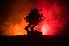 Silhouet van reuzerobot Futuristische tank in actie met de mistige achtergrond van de brandhemel royalty-vrije stock fotografie