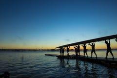 Silhouet van roeiers bij zonsopgang Stock Foto's