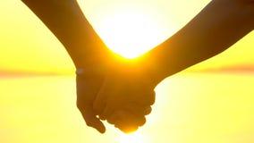 Silhouet van romantisch gelukkig paar, twee Minnaars, de jonge mens en de handen van de vrouwenholding bij oceaankust bij zonsond stock video