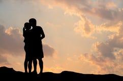 Silhouet van romantisch paaromhelzing het kussen tegen een zonsonderganghemel Stock Foto