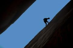 Silhouet van rotsklimmer het rappelling Stock Foto's