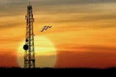 Silhouet van satellietcommunicatieantenne met de zonsondergang Stock Foto's