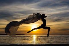 Silhouet van slank sexy meisje die in bikini met sjaal op springen Stock Foto