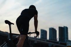 Silhouet van sportman berijdende fiets naast glasvoorgevels van wolkenkrabbers royalty-vrije stock afbeelding