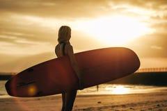 silhouet van surfer het stellen met surfplank op strand bij zonsondergang royalty-vrije stock fotografie