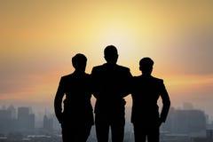Silhouet van teamzakenlieden die bovenop de bouw vastlopen en royalty-vrije stock foto's