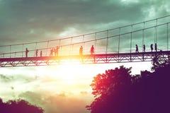 Silhouet van toerist op hangbruggang aan de wildernis Stock Foto's