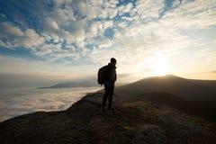 Silhouet van toeristenwandelaar met rugzak die zich op de bovenkant van de berg bevinden en de mooie gele herfst bekijken Royalty-vrije Stock Foto