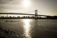 Silhouet van Triborough-brug over de rivier en de stad in donkere uitstekende stijl Stock Foto's