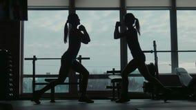 Silhouet van twee aantrekkelijke vrouwen die de oefening van de hurkzitgeschiktheid in een gymnastiek doen stock videobeelden