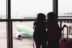 Silhouet van twee Aziatische kindmeisjes met rugzak die vliegtuig bekijken en op het inschepen in de luchthaven wachten stock fotografie