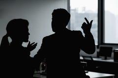 Silhouet van twee bedrijfsmensen die en in het bureau gesturing debatteren Royalty-vrije Stock Afbeeldingen
