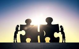 Silhouet van twee bedrijfsvrouwen die raadsel verbinden Stock Foto