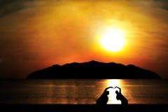 Silhouet van twee mensen tot die hartvorm bij zonnen worden gemaakt Royalty-vrije Stock Foto's