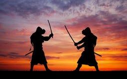 Silhouet van twee samurais in duel stock foto