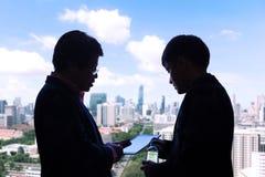 Silhouet van twee uitvoerende zakenlieden die over een projec bespreken stock afbeeldingen