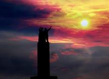 Silhouet van twee vrienden in bovenkant van een monument Stock Fotografie