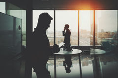 Silhouet van twee zakenlieden in bureaubinnenland stock fotografie