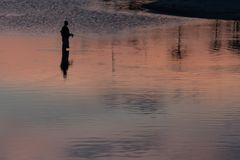 Silhouet van unrecognisable visser in het meer royalty-vrije stock afbeelding