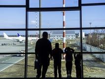 Silhouet van vader en babyjongens die op groot venster kijken stock foto