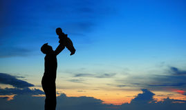 Silhouet van vader en kind op de zomerzonsondergang Stock Afbeelding