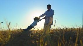 Silhouet van vader en zoon die en van zonsondergang op tarwegebied spelen genieten in aard op de zomerdag Het gelukkige Lopen van stock footage