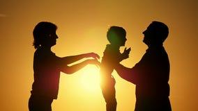 Silhouet van vader van moeder en kind De moeder gaat de vader van het kind tot de zonsondergang in een langzame motie over E stock video