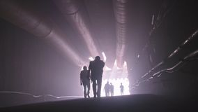 Silhouet van vele bouwvakkers die van een grote tunnel opstappen stock videobeelden