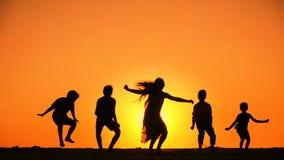 Silhouet van vijf jonge geitjesfamilie die bij zonsondergang springen stock videobeelden