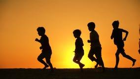 Silhouet van vijf jonge geitjesfamilie het runniing bij zonsondergang stock videobeelden