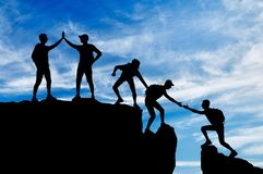 Silhouet van vijf klimmers die de slaafsheid van het werken in een team overwinnen stock fotografie