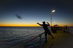 Silhouet van visser met hoed die vissen netto status op overzees dok werpen die bij zonsondergang met mooie oranje hemel in vakan Stock Foto's