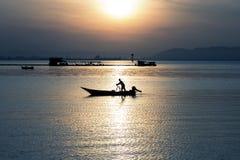 Silhouet van visser op boot stock foto