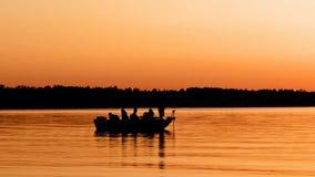 Silhouet van vissersboot op kalm meer na zonsondergang stock videobeelden