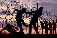 Silhouet van vluchtelingen en prikkeldraad royalty-vrije stock afbeelding