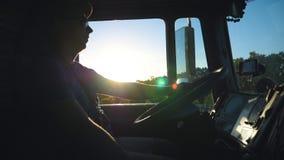 Silhouet van vrachtwagenbestuurder het drijven door platteland in avond Mens die in zonnebril zijn aandachtige vrachtwagen contro stock videobeelden