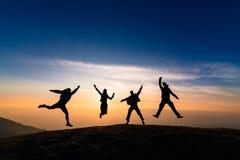 Silhouet van vrienden die in zonsondergang voor geluk, pret springen en te royalty-vrije stock afbeelding