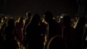 Silhouet van vrouw en mens die zich in menigte bevinden en bij nacht de wachten stock video