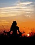 Silhouet van vrouw in lotusbloemmeditatie op zonsondergangachtergrond yoga Stock Foto's