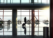 Silhouet van vrouw met bagage tegen grote vensters Royalty-vrije Stock Afbeelding