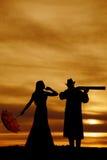 Silhouet van vrouw met paraplu en kerel met kanon Royalty-vrije Stock Afbeelding