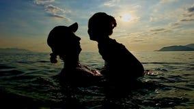 Silhouet van Vrouw met Peuter in Wapens in Overzees tegen Zonsondergang stock videobeelden