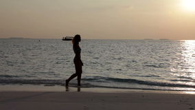 Silhouet van vrouw tegen een zonsondergang bij oceaan stock footage
