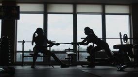 Silhouet van vrouw twee die een kabel in een sportfitness gymnastiek trekken stock videobeelden
