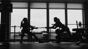 Silhouet van vrouw twee die een kabel in een sportfitness gymnastiek trekken stock footage