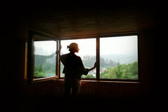 Silhouet van vrouw in zonneschijn bij groot houten venster met mening o stock foto