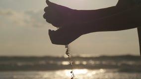 Silhouet van vrouwelijk hand gietend overzees zand door haar vingers bij zonsondergang tegen een oceaanachtergrond Wapen van jong stock video