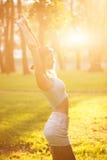 Silhouet van vrouwelijk model in zonlicht in park in openlucht ademend verse lucht Gezond Actief Levensstijlconcept Portret Royalty-vrije Stock Afbeeldingen