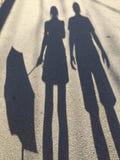 Silhouet van vrouwen die een paraplu houden en een man die zich naast haar bevindt stock afbeeldingen